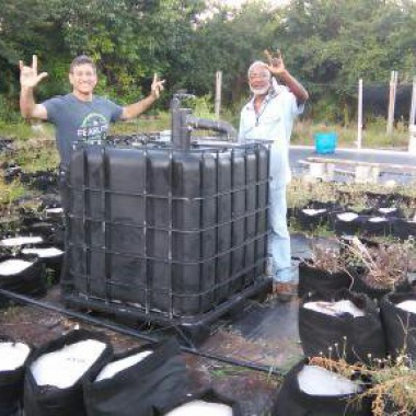 T.H.and Alex celebrate the siting of Alex's new IBC Biodigester as the liquid composting centerpiece to his garden education center.