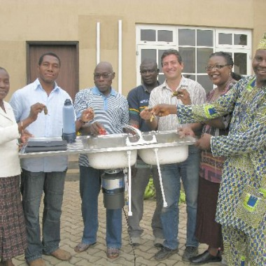 Former Nigerian President Oluwasegun Obasanjo demonstrates the Insinkerator Food Waste Grinder that Emerson Electronics gave him as a gift to use with his home biodigester.