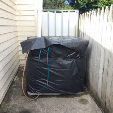 Insulation wrapped in black plastic to keep water out